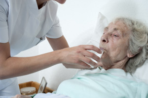 Altenpflegerin reicht wasserglas